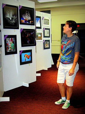 """Wide Angle Photo Club member Raili Ruul views the photo exhibit at last year's """"Power of Photography Show."""""""