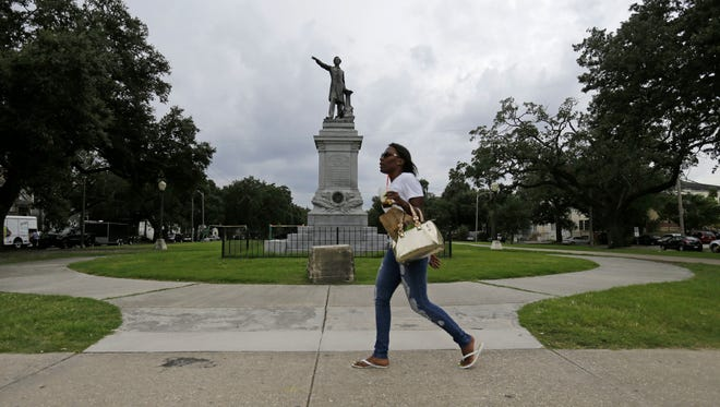 FILE - In this Sept. 2, 2015, file photo, a woman walks past a monument of Jefferson Davis on Jefferson Davis Parkway at Canal Street in New Orleans. The statue of Davis was removed by the city in May 2017. A spokesman for the city told the AP on May 19, 2017, that a story circulating online that the statue would be replaced with one of former President Barack Obama is false. (AP Photo/Gerald Herbert, File)