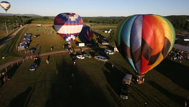 Balloons inflate as they prepare to take off Saturday during the early morning launch of the Empire Balloon Festival at Barton Orchards in Poughquag.
