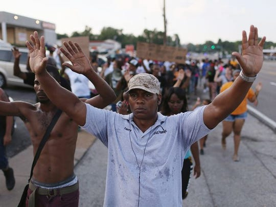 """Demonstrators protesting the shooting death of Michael Brown chant, """" Hands up, Don't Shoot"""", as they make their voices heard in Ferguson, Mo."""