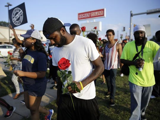 Protesters move down the street, many carrying roses in Ferguson, Mo.