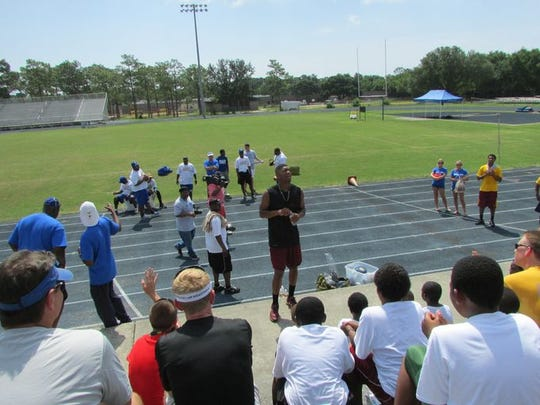 Heisman Trophy-winning Florida State quarterback Jameis Winston, standing center, addresses the crowd at the Charlie Ward Mentor Leadership Camp, June 14, 2004.