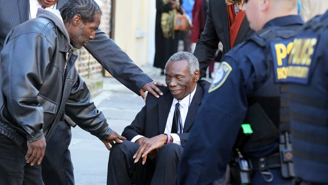 John Pinckney, father of shooting victim Rev. Clementa Pinckney, is greeted after leaving J. Waites Waring Federal Courthouse in Charleston, S.C., Thursday, Dec. 15, 2016, where Dylan Roof was found guilty of all 33 federal charges in the Emanuel AME Church shootings.