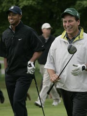 Tiger Woods, left, walks with MSU  basketball coach