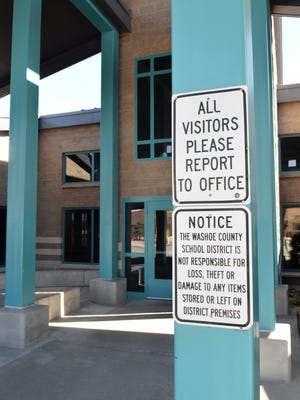 A sign near the entrance of Spanish Springs Elementary School directs visitors to check in at the front office.