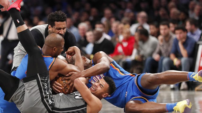 Brooklyn Nets guard Timothe Luwawu-Cabarrot grapples for the ball with Oklahoma City guards Chris Paul, left, and Deonte Burton.