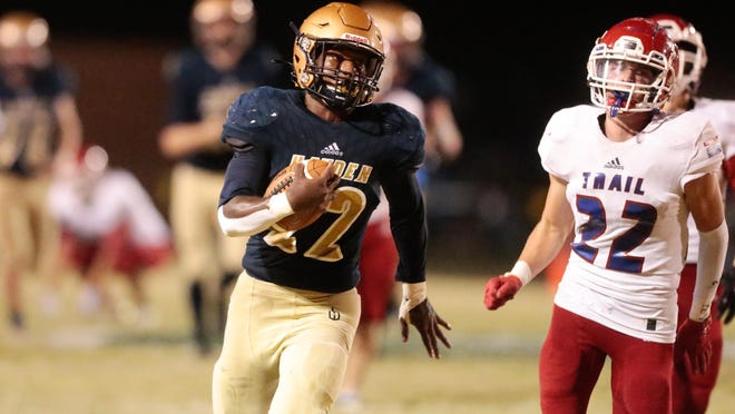 Hayden senior Desmond Purnell runs past Santa Fe Trail defenders to score a touchdown in the second quarter of Friday's game at Hayden. Purnell ran for 178 yards and two touchdowns as the Wildcats won 49-14.