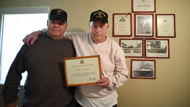 Cold War veterans Lynn Olson, 75, of Salem Township and Tom Cameron, 76, of Troy hold up Cameron's Certificate of Recognition for his service in the U.S. Army.