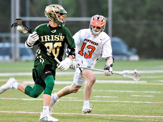 York Catholic's Brennan Witman, left, drives the ball while Central York's Logan Paluch defends during York-Adams League boys' lacrosse championship action at Horn Field in Red Lion, Friday, May 11, 2018. The Irish have advanced to the state 2-A semifinals. Dawn J. Sagert photo