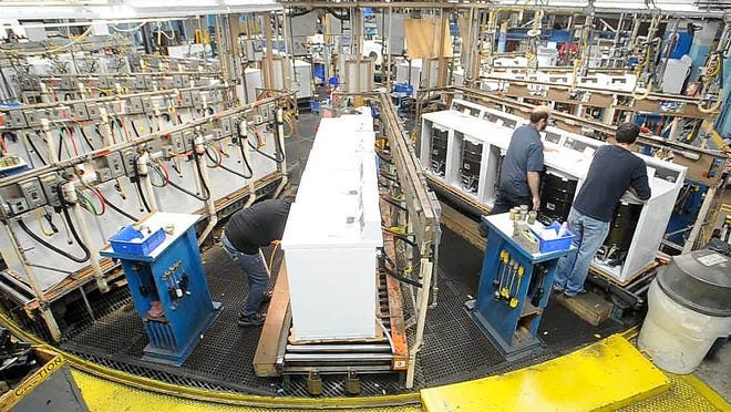 Employees at Alliance Laundry Systems test  washers before being boxed and shipped in December 2014.