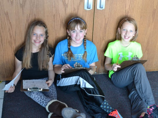 Izabel Paape, from left, Lauren Maki and Lola Teatz work together to write and illustrate a story. They are students in Alyssa Breu's fifth-grade class at Grant Elementary School in Marshfield.
