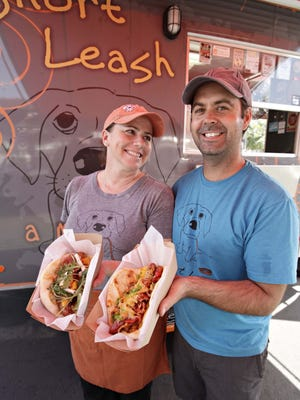 Kat and Brad Moore, owners of Short Leash Hotdogs, hold their Sunny Combination and Devil Dog Combination menu items.