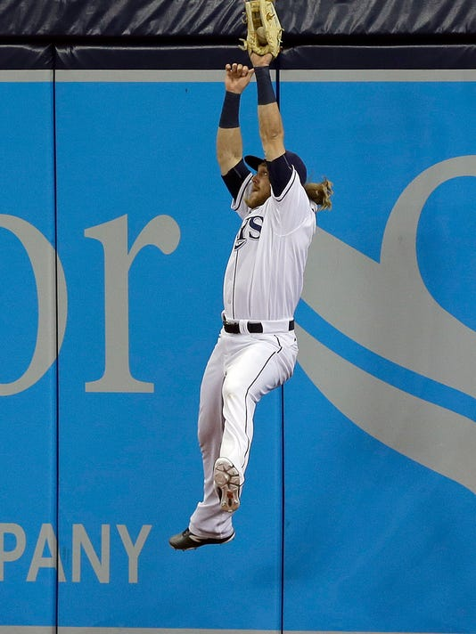 Tampa Bay Rays right fielder Taylor Motter leaps high in the air to make the catch on an RBI sacrifice fly by Seattle Mariners' Adam Lind during the seventh inning of a baseball game Tuesday, June 14, 2016, in St. Petersburg, Fla. (AP Photo/Chris O'Meara)