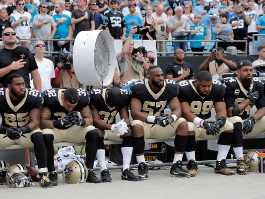 New Orleans Saints players sit on the bench during the national anthem before an NFL football game against the Carolina Panthers in Charlotte, N.C., Sunday, Sept. 24, 2017. (AP Photo/Bob Leverone)