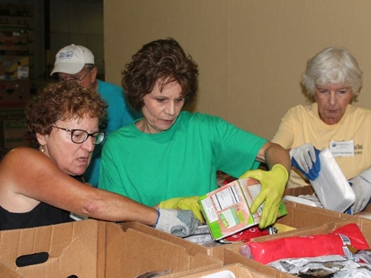 Maureen Yuster, middle, packs frozen meat at the Harry Chapin Food Bank. Volunteering with her are Fran Darpino, left, and Carol Hampton, right.