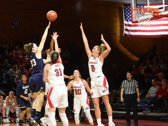 Navy's Molly Sanders takes a shot over Marist defenders at McCann Arena in Poughkeepsie on Friday.