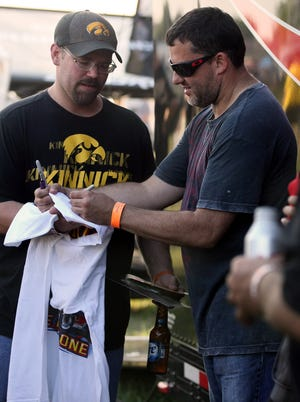 Tony Stewart autographs a shirt for Jeremy Hayes of Montezuma at Southern Iowa Speedway on Aug. 5, 2013 in the Front Row Challenge at Oskaloosa.
