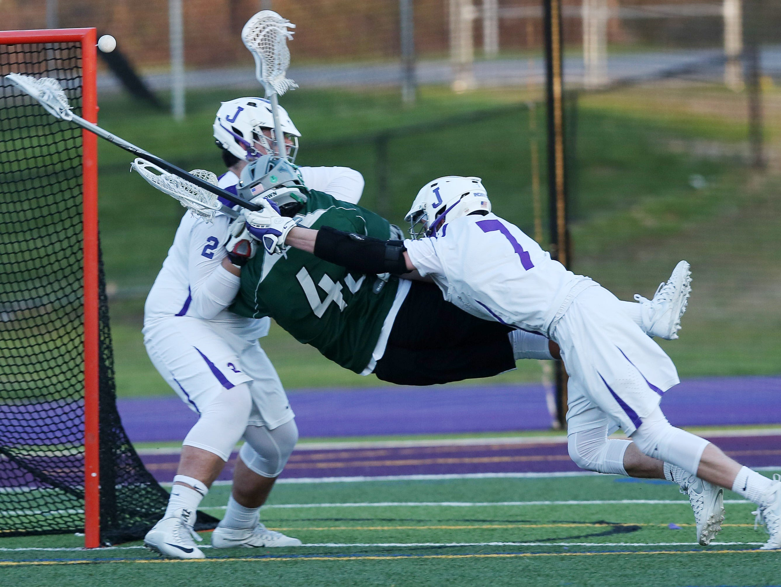 Yorktown's Justin Cavallo (43) gets hit by John Jay's Shahe Katchadurian (2) and Jake Murphy (7) as he gets off a shot that went for a second half goal breaking a 5-5 tie, during a boys lacrosse game at John Jay High School in Cross River April 14, 2016. Yorktown won the game 9-7.