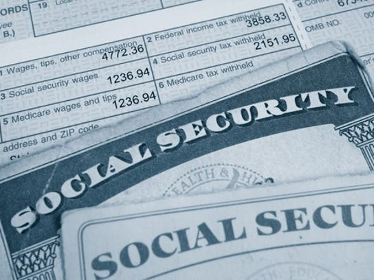 Social Security cards laid atop a pay stub, highlighting payroll taxes paid.