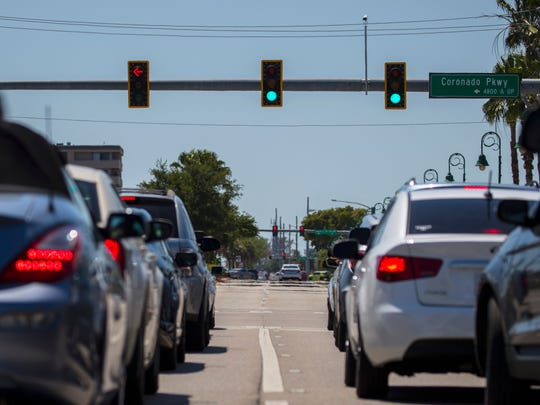 Vehicles along Cape Coral Parkway begin to travel west after waiting for the traffic signal at Coronado Parkway in Downtown Cape Coral on Tuesday, April 18.