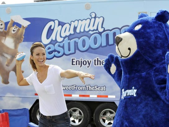Person throwing a mini-football to the Charmin mascot in front of a semi truck with Charmin marketing on it.