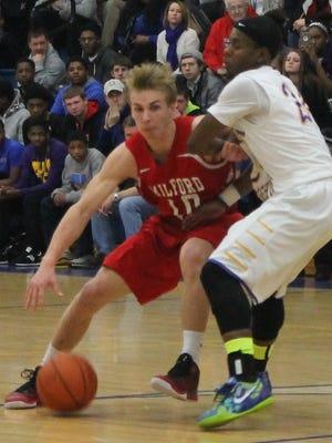 Milford junior guard Brad Hall works against Northwest's Kobe Brown.