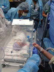 Maria Tompkins, shortly after birth, reaches her arm through the incubator to touch her mother's hand.