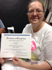 Melissa Nelson holds her Certificate of Completion