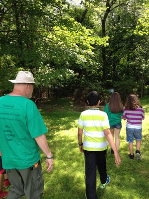 David Thompson takes a few of his fellow trailblazers to the area where the Voorhees Middle School Trailblazers Club would like to create a trail.