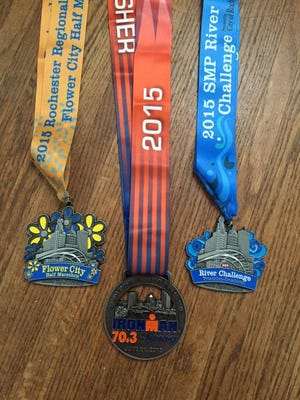 Jim McLaughlin's Syracuse Ironman medal pictured next to his 2015 Flower City Challenge medals.