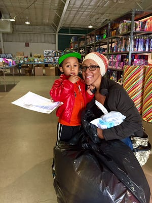 Melissa Moala, 31, of Reno, holds a bag of gifts on Saturday after shopping as part of the 19th annual Christmas on the Corridor.