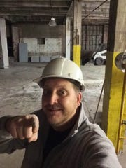 Jerry Sutherlin, who is opening Round Town Brewing, poses at the construction site for his new brewery.
