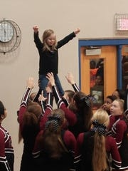 Alayna Scallion performs a stunt with the support of the members of the Crockett Middle School cheerleading team.