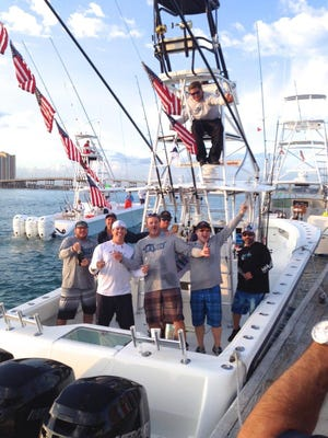 """Capt. Art Sapp, in the boat's tower, along with boat owner Keith McDonald and their fishing team, celebrate the """"Liquid's"""" win in the 79th-annual Silver Sailfish Derby held Jan. 7-8 out of West Palm Beach. They scored 11 sailfish releases in the two days and they used United States flags as pennants to signify their catches."""