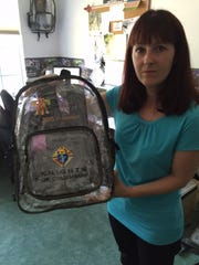 Linda Milano of CFB Promotional Products, poses with a backpack her firm designed for upcoming World Meeting of Families in Philadelphia.