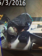 Macomb County Treasurer's Office surveillance photos show a man climbing under the security glass at the clerk's counter.
