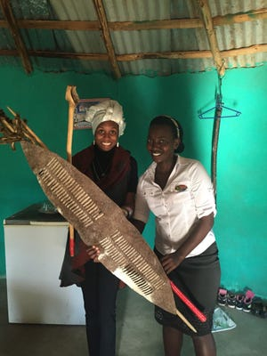 Ri'Cha ri Sancho visits a school in South Africa, where a student displays a tribal shield.