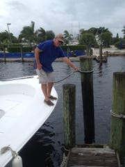 Don Long secures a friend's boat to a dock at the Manatee Marina in Port Salerno.