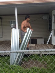 Alex LoFiego puts the finishing touches on the storm shutters on his house in the Ridgeway subdivision in Hobe Sound.