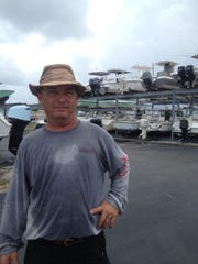 Chris Howell, the yard manager at Blowing Rocks Marina in Tequesta, tied down boats to racks in advance of Hurricane Matthew.