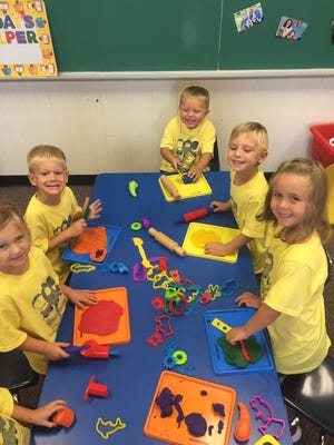 St. Paul Catholic School Preschoolers Emma Lux, Michael Resing, Wesley Allwell, Miles Popil and Paizley Chance have fun with Play-Doh.