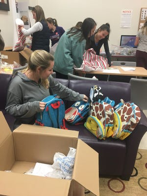 Shown are students of Clemson University International Reading Association Student Council, packing bags Christmas bags for children to enjoy.