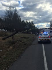 A state police cruiser is parked next to a telephone pole on Route 72 in Swatara Township that was sheared in half shortly after noon Friday, by the work van in front of it.