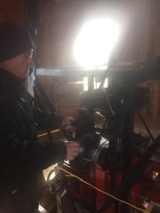 Jay McGinnis demonstrates one of the windmills on his New Park farm.