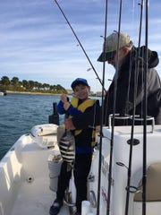 Alex holds up a nice sheepshead that he caught while fishing with his dad, Bob, on a cool morning. the 7-year-old had a fun morning catching lots of fish!