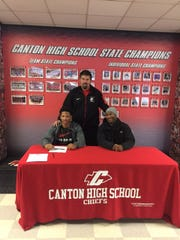 Canton seniors Markus Sanders (seated, from left) and Cameron Goode take part in National Signing Day ceremonies. Standing is Chiefs head coach Tim Baechler.
