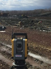 A surveying tool called a theodolite points to contractors working in trenches at the construction site of Northwest Elementary School in Aspens Business Park.