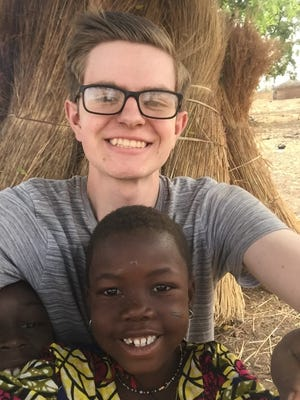 Micah Musser, a 2015 graduate of Elco High School, poses for a photo with villager in Labariga, Ghana.