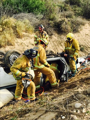 Ventura city firefighters work to remove a man from an overturned truck discovered in the river bottom off southbound Highway 33 in Ventura Friday morning.