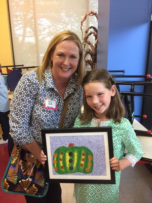 Poplar Grove Elementary School student Ava Baer, left, displays her artwork with art teacher Kelly Salfe.